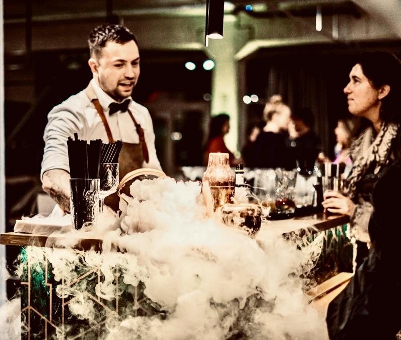 Cocktailshaker achter een cocktailbar die open is voor bar verhuur waar hij verschillende cocktails maakt