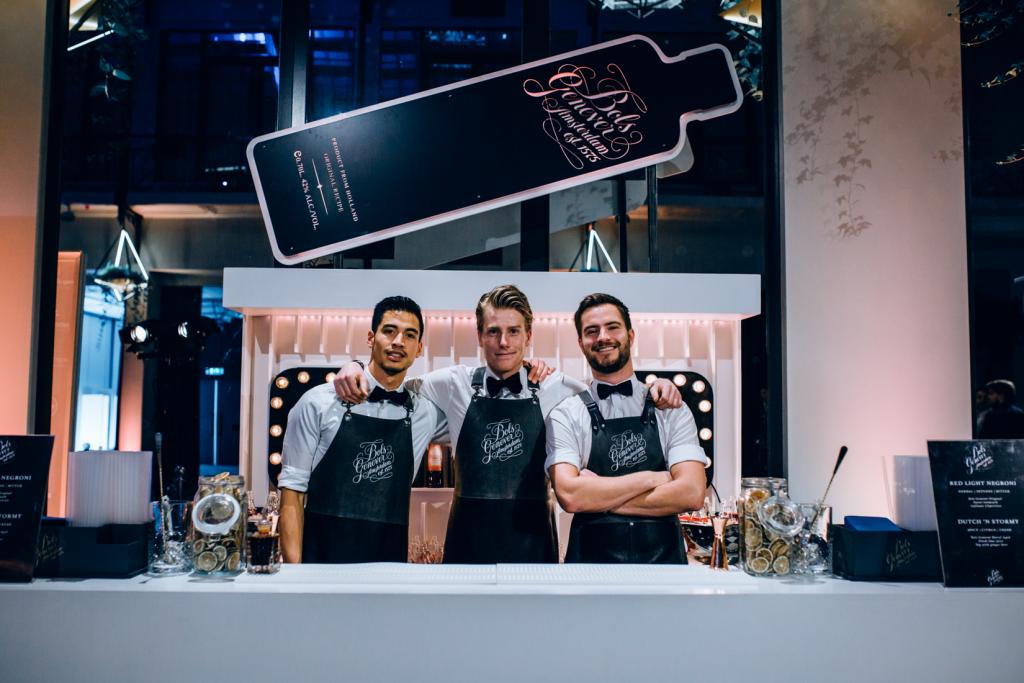 Bartenders en cocktailshakers achter een cocktail bar
