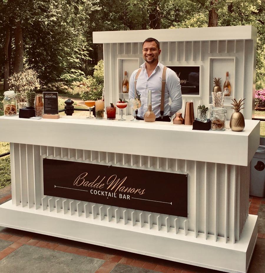 Cocktailshaker achter mooie witte luxe cocktailbar op een bruiloft